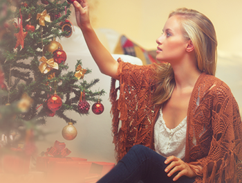 girl hanging decorations on christmas tree